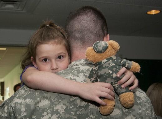 uniformed soldier hugging daughter